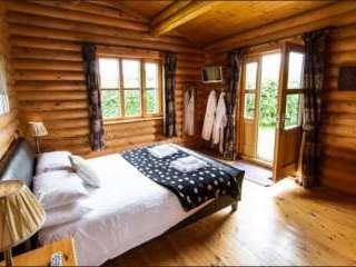 Chaffinch Lodge Bedroom with Romantic Leather Sleigh Bed and Doors to the Private Hot Tub