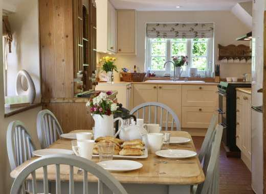 A Lovely Country Kitchen With Electric Range Cooker and Breakfast Table