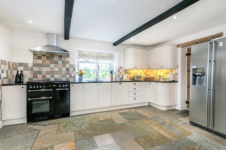 Modern well-equipped kitchen with granite work top and slate flooring