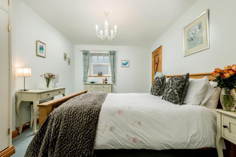 oak bed in a pale blue room