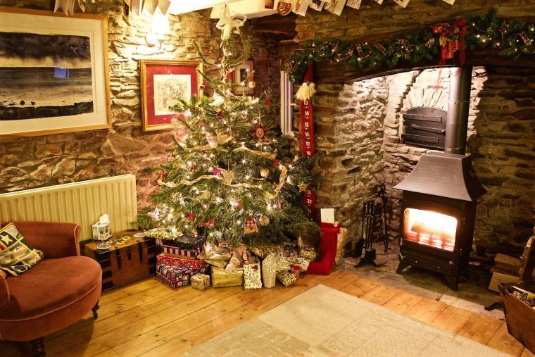 Barnfield's lounge at Christmas with a Christmas tree by the inglenook surrounded by presents