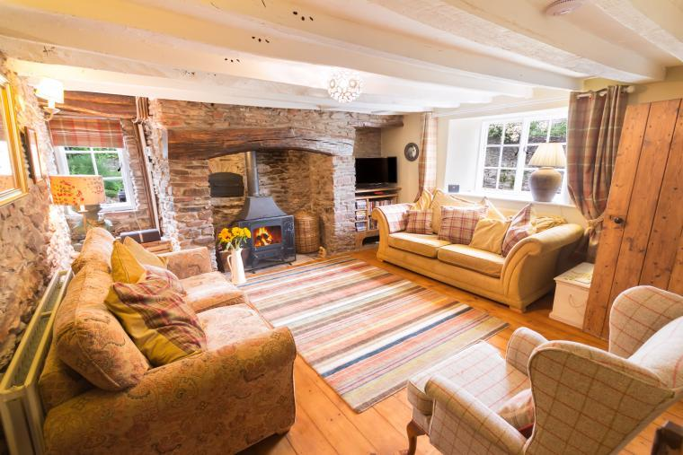 A comfortable Exmoor country cottage lounge with oak beams, pine floor and a  large inglenook with woodburner