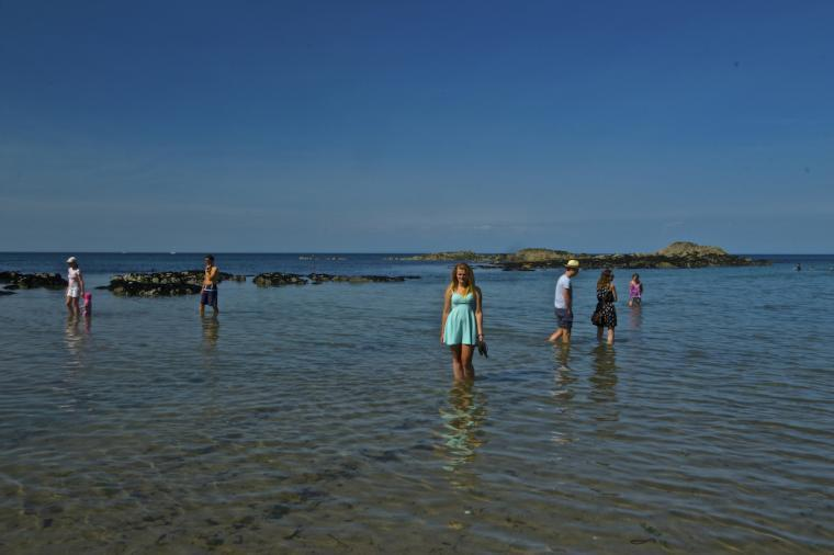 People paddling in the sea at Lee Bay on a sunny afternoon