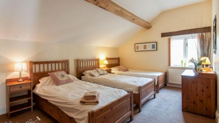 Triple bedroom with 3 single beds and cot