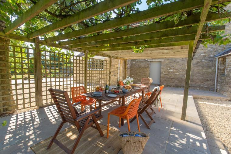 Leafy arbour with outdoor dining area