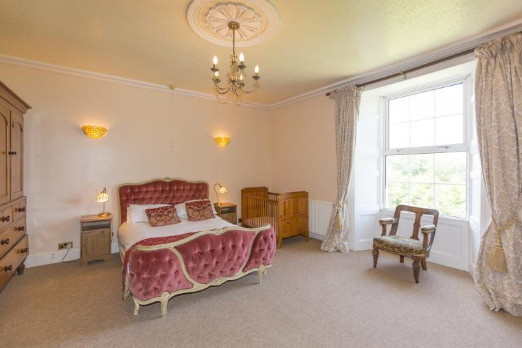 Double bedroom with cot and distant sea views