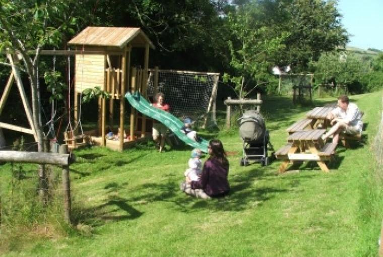 Self-catering country cottage with play area, Wendy House, sandpit, swings, slide, toddlers kick about area adjacent to the orchard