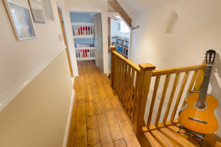 A cottage landing with pine floors and bannister rails