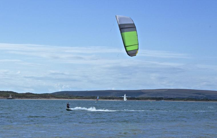 A kite surfer races across the surf off Instow Beach in North  Devon
